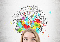 Concept of a successful business. Close up of a woman's head. She is looking at a bright creative start up idea drawing on a concrete wall. Concept of a Royalty Free Stock Images