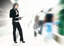 Concept of a successful businesswoman with suit, standing holding book and over exposed abstract background royalty free stock photo