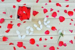 Concept with sugared almond. Word love written with sugared almond , single stone ring in wooden box, sugared almond in flower bouquet and red rose petals on stock images