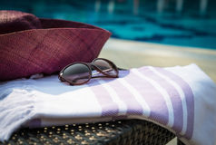 Concept of summer accessories close-up of white and purple Turkish towel, sunglasses and straw hat. Royalty Free Stock Photography