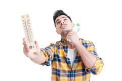 Concept of summer high temperature with man holding thermometer Royalty Free Stock Photos