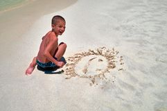 Concept summer rest by the sea. Laughing boy looks at camera sitting on sand in surf line. Cute child painted a smiley sun face.  stock photo