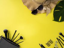 Makeup Bag with variety of beauty products yellow background royalty free stock photos