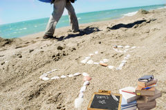Concept of summer: sea written with the shells on the sand. Concept of summer and school`s end with the word sea made with the shells on the sand and some books Stock Photo