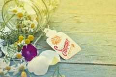Concept of summer time with color toning. Concept of summer time: flowers in a glass jar with the tag `Summer` on a painted wood background. Photo with color Royalty Free Stock Photo