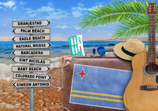Concept of summer traveling with old suitcase and Aruba town sign Royalty Free Stock Image