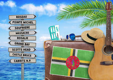 Concept of summer traveling with old suitcase and Dominica town Stock Images