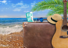 Concept of summer traveling with old suitcase and guitar Stock Image