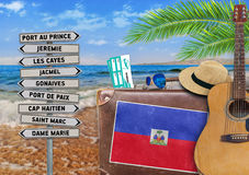 Concept of summer traveling with old suitcase and Haiti town sign Stock Photos