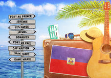 Concept of summer traveling with old suitcase and Haiti town sign Royalty Free Stock Photography