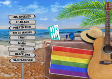 Concept of summer traveling with old suitcase and LGBT flag royalty free stock photography