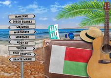 Concept of summer traveling with old suitcase and Madagascar town Royalty Free Stock Images