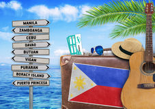 Concept of summer traveling with old suitcase and Philippines. Town close Stock Photography