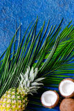 Concept of summer tropical fruits. Pineapple, coconut and palm branch on blue table background top view copyspace Royalty Free Stock Photo