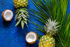 Concept of summer tropical fruits. Pineapple, coconut and palm branch on blue table background top view copyspace Stock Image