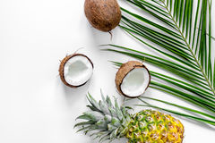 Concept of summer tropical fruits. Pineapple, coconut and palm branch on white background top view copyspace Stock Images