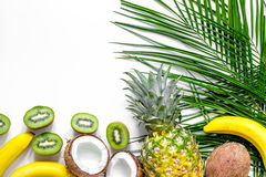 Concept of summer tropical fruits. Pineapple, kiwi, banana, coconut on white background top view copyspace Stock Photography