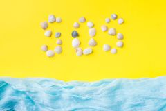 The concept of summer vacation. Seashells yellow background Blue scarf imitation sea Text of shells SOS. The concept of summer vacation. Seashells yellow Stock Images