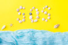 The concept of summer vacation. Seashells yellow background Blue scarf imitation sea Text of shells SOS. The concept of summer vacation. Seashells yellow Royalty Free Stock Photography
