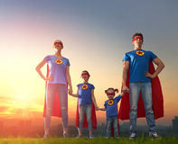 Concept of super family. Mother, father and their daughters are playing outdoors. Mommy, daddy and children girls in an Superhero`s costumes. Concept of super Stock Photo