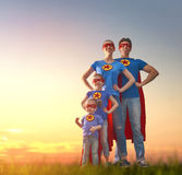 Concept of super family. Mother, father and their daughters are playing outdoors. Mommy, daddy and children girls in an Superhero`s costumes. Concept of super Stock Image