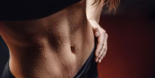 Concept sweat after exercise. Inflated body fitness of young woman, abdominal muscles dices.  stock image