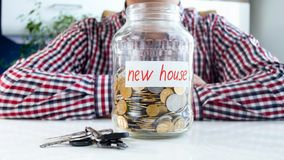 Concept of taking bank loan for buying new house. Man with glass jar full of money and keas from new apartment on white. Concept of taking bank loan for buying stock photography