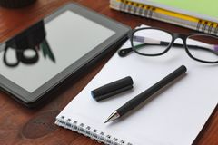 Pen, open notebook, tablet computer and glasses on office desk.The concept:Teacher`s Day or the beginning of work or project. Stock Photos