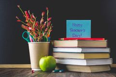 Concept of Teacher's Day. Objects on a chalkboard background. Books, green apple, plaque: Happy Teacher's Day, pencils and pens  Stock Image