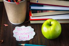 Concept of Teacher's Day. Objects on a chalkboard background. Books, green apple, plaque: Happy Teacher's Day, pencils and pens  Royalty Free Stock Image