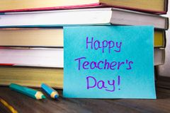 Concept of Teacher's Day. Objects on a chalkboard background. Books, green apple, plaque: Happy Teacher's Day, pencils and pens  Stock Photos