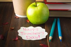 Concept of Teacher's Day. Objects on a chalkboard background. Books, green apple, plaque: Happy Teacher's Day, pencils and pens  Royalty Free Stock Photo