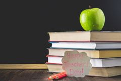 Concept of Teacher's Day. Objects on a chalkboard background. Books, green apple, plaque: Happy Teacher's Day, pencils and pens  Royalty Free Stock Photos