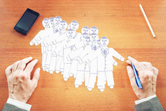 Concept of team building. Abstract image with a man making human characters on the table Stock Photography