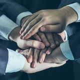 Concept of team work:a close-up of hands of business teams, stacked one on another. Close-up of hands of business teams, stacked one on another.photo on a black Royalty Free Stock Photography