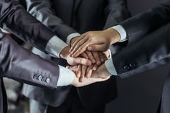 Concept of team work:a close-up of hands of business teams, stacked one on another. Close-up of hands of business teams, stacked one on another.photo on a black Stock Image