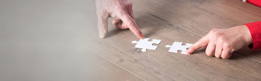 Concept of teamwork. Hands joining two puzzle pieces, teamwork concept Royalty Free Stock Photography