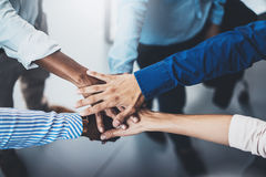Concept of teamwork.International business team showing unity with their hands together. Horizontal,blurred background Stock Images