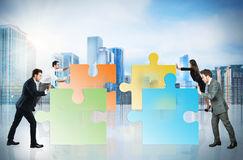 Concept of teamwork and partnership with businesspeople and puzzle. Royalty Free Stock Photo