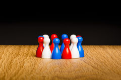 Concept teamwork red white blue. Concept for teamwork. Red white blue pawn figures and black background on wooden surface. National three colors of flag Croatia royalty free stock photography