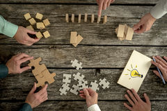 Concept of teamwork, strategy, vision or education. Businessmen planning business strategy while holding puzzle pieces, creating ideas with light bulb drawn on Stock Photography