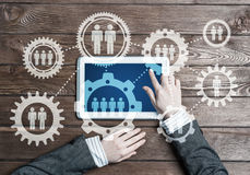 Concept of teamworking and connection with gears mechanism and tablet pc Stock Images