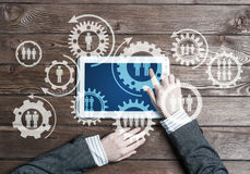 Concept of teamworking and connection with gears mechanism and tablet pc Royalty Free Stock Photos