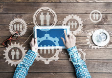 Concept of teamworking and connection with gears mechanism and tablet pc Royalty Free Stock Photo