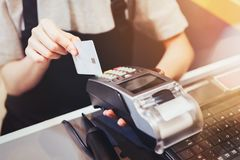 Concept of technology in buying without using cash. Close up of hand use credit card swiping machine to pay.  stock photo