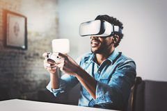 Concept of technology,gaming,entertainment and people.African man enjoying virtual reality glasses while relaxing in stock images