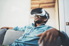 Concept of technology,gaming,entertainment and people.Bearded african man enjoying virtual reality glasses headset or 3d Stock Photo