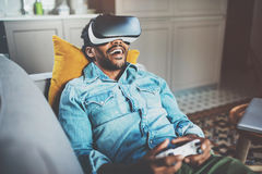 Concept of technology,gaming,entertainment and people.Bearded african man enjoying virtual reality glasses while Stock Photography