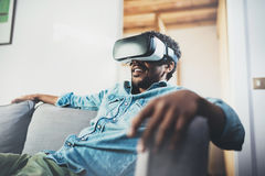 Concept of technology,gaming,entertainment and people.Young african man enjoying virtual reality glasses headset or 3d Royalty Free Stock Photography