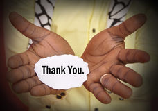 CONCEPT OF THANKS. Image of a businessman holding a piece of paper in his hands with the word thank you as concept of thanks stock image